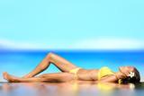 Sunbathing woman relaxing under sun in luxury poster