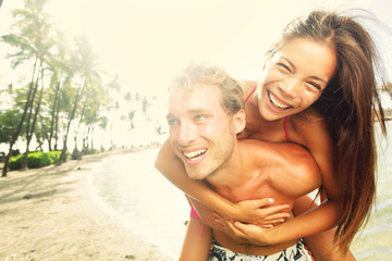 Happy young joyful couple beach fun laughing