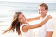 Happy couple on beach in love having fun