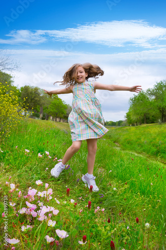 happy children girl jumping on spring poppy flowers