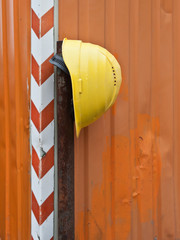 Ein gelber Schutzhelm vor einem orangen Container