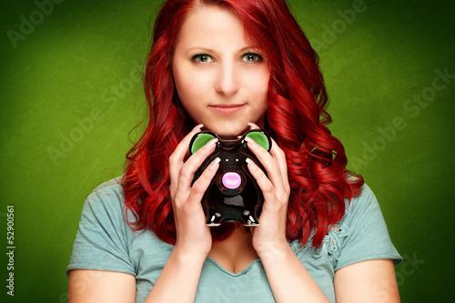 Frau mit Sparschwein vor grünem Hintergrund