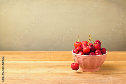 Bowl full of cherries on wooden table over grunge background