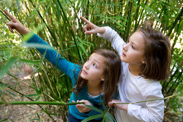 sister twin girls playing in nature pointing finger