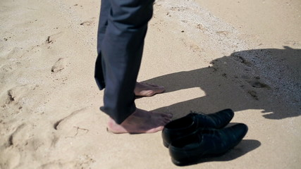 Businessman barefoot legs standing on the beach