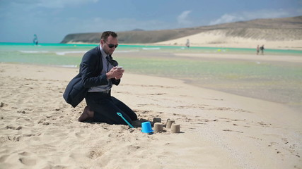 Businessman playing on the beach and talking on cellphone