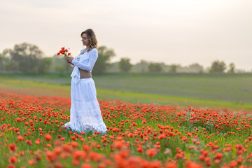 girl in a white dress in the poppy field