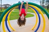 children kid girl upside down on a park ring