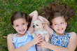 twin sisters playing with chihuahua dog lying on lawn