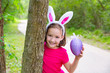 Easter girl with big purple egg and funny bunny ears