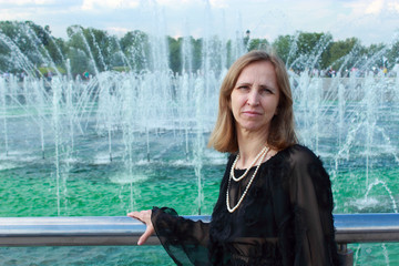 A woman stands near a fountain