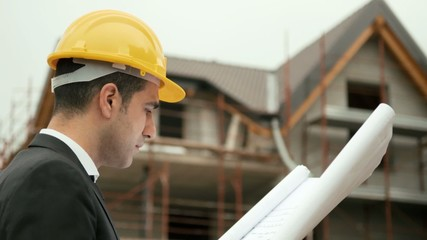 Man working, architect in construction site with building plans