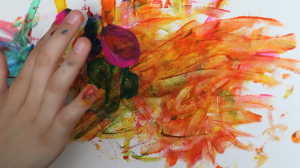 Little baby girls hands painting colorfull flower