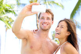 Vacation couple taking pictures with camera phone