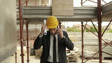 Engineer talking on mobile phone, walking in construction site