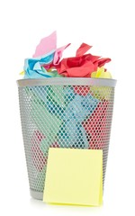 A waste paper bin with coloured paper on a white background