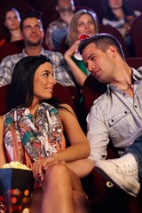 Romantic couple sitting at movie theater