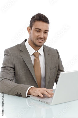 Happy businessman working on laptop