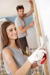 Attractive woman renovating house smiling