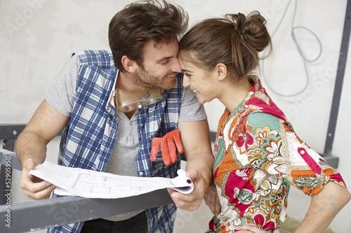 Happy couple with floor plan