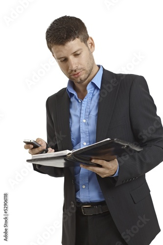 Young businessman looking at organizer