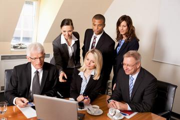 Kollegen schauen auf einen Laptop