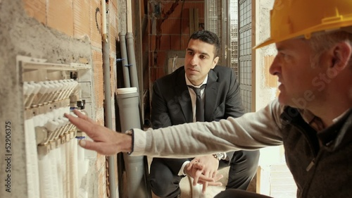 Plumber talking to architect in construction site, new building