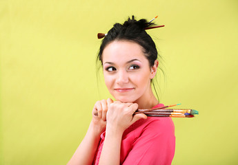 Beautiful young woman painter with brushes, on color background