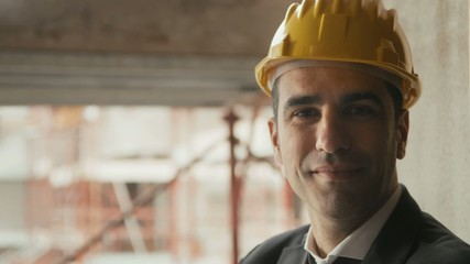 Engineer with helmet smiling in construction site, portrait