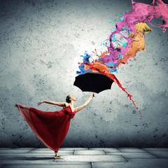 Ballet dancer in flying satin dress with umbrella