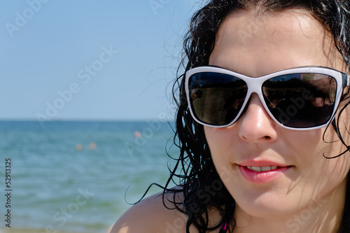 Woman in sunglasses posing at the sea
