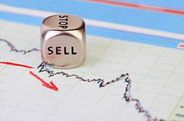 Downtrend financial market chart with red arrow and dices cube w