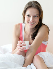 Junge, sportliche Frau trinkt Wasser zum Frühstück im Bett