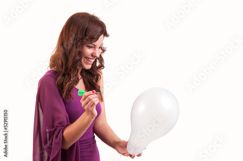 Happy young girl is going to break a balloon with a dart on whit