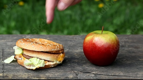 Man's hand near burger and apple episode 2