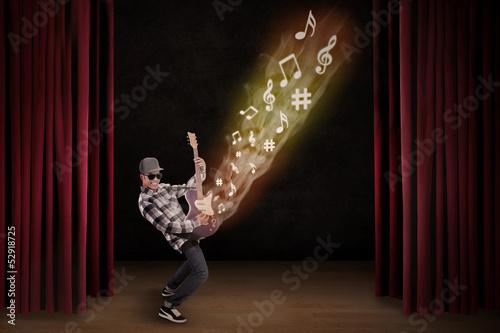 Artist perform guiter instrument on stage