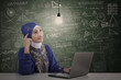 Asian female muslim with laptop under lit bulb