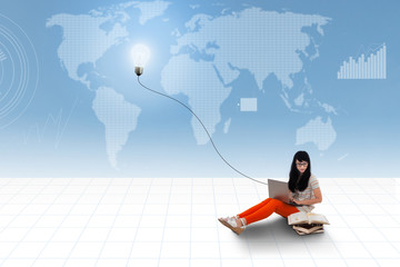 Asian student using laptop on world map background