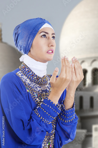 Attractive muslim girl praying at mosque