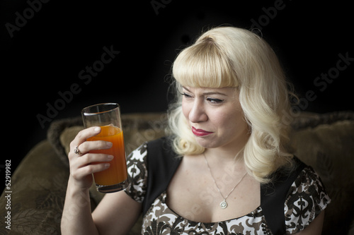 Beautiful Young Woman with Blond Hair Drinking Mango Juice