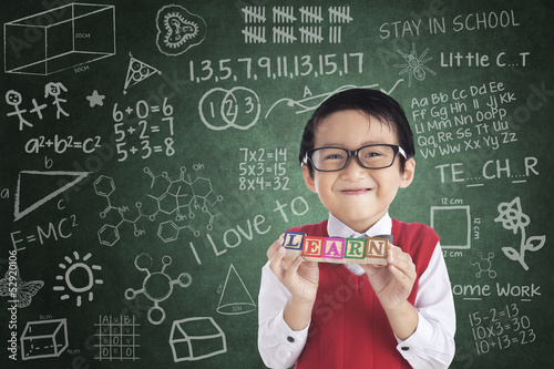 Cheerful boy student holding LEARN block