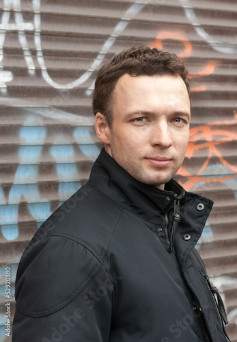Portrait of young Caucasian man in black with graffiti