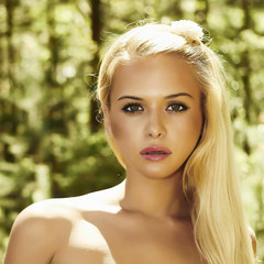 Beautiful blond woman in forest. summer sunlight