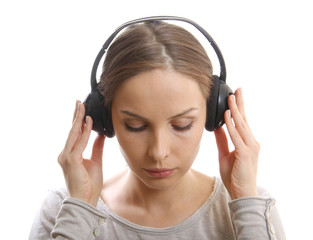Young woman listening music with headphones, on white