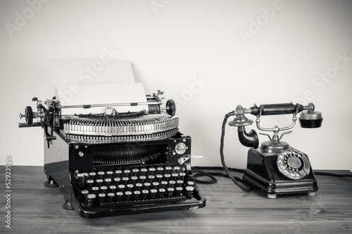 Vintage telephone, old typewriter on table desaturated photo