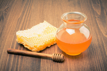 Honeycomb and honey pot on wooden table. Vintage toned
