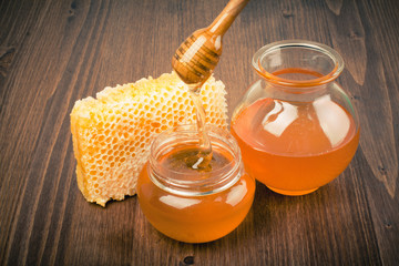 Honeycomb and honey pot, dipper on wooden table