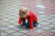 Preschooler child drawing with chalk on sidewalk
