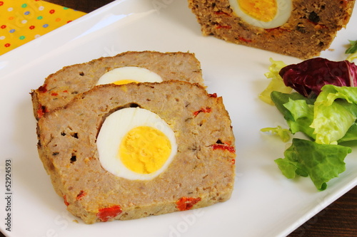 Sliced meatloaf with boiled egg, red pepper and capers