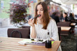 Young woman eating sushi in a restaurant garden